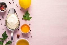 Sauce et ingrédients à mayonnaise sur le fond rose de tissu Image libre de droits