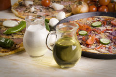 Sauce et trois pizzas Image stock