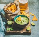 Sauce fraîche à guacamole dans la cuvette en céramique bleue, puces de maïs, bière Photos libres de droits
