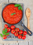 Sauce From Heirloom Tomatoes. A cast iron pan filled with tomato sauce made from organic, heirloom tomatoes, resting on a piece of vintage salvaged slate, circa stock photography