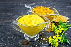 Sauce mustard in two sauceboats with flower on black board stock image