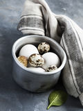 Sauce pan with raw hen and quail eggs. Metallic sauce pan with raw hen and quail eggs on dark shabby background Royalty Free Stock Photography