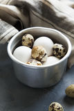 Sauce pan with raw hen and quail eggs. Metallic sauce pan with raw hen and quail eggs on dark shabby background Stock Photos