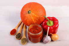 Sauce of pumpkin in glass jar, spices and ingredients on wooden table Stock Image