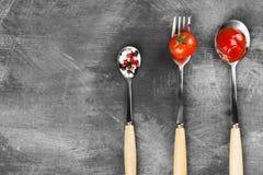 Sauce tomate, cerise, épices dans la fourchette et cuillères sur un backgr foncé Photographie stock libre de droits