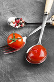 Sauce tomate, cerise, épices dans la fourchette et cuillères sur un backgr foncé Photos libres de droits