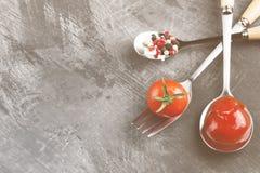 Sauce tomate, cerise, épices dans la fourchette et cuillères sur un backgr foncé Photo stock