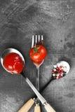 Sauce tomate, cerise, épices dans la fourchette et cuillères sur un backgr foncé Photographie stock