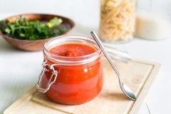 Sauce tomate dans le pot sur le Tableau en bois blanc Photographie stock libre de droits