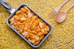 Sauce tomate de macaronis avec l'endroit de poulet dans la casserole Image libre de droits
