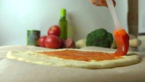 Sauce tomate de propagation d'homme au-dessus de base de la pâte Cuisson de la pizza faite maison, une partie de l'ensemble fin 4 banque de vidéos