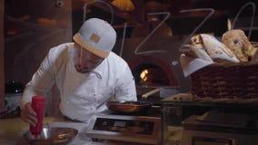 Sauce tomate de versement de cuisinier professionnel sur la gauffreuse Concept à cuire gastronome banque de vidéos