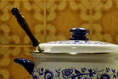 Saucepan. A Saucepan on a stove with wall tiles in the background Royalty Free Stock Photo