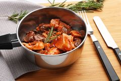 Saucepan with chicken cacciatore. On wooden board Stock Images