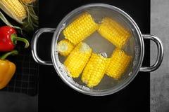 Saucepan with corn cobs. On stove Stock Photo