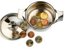Saucepan and euro coins. A pot with a few euro coins symbol photo for sovereign debt and financial crisis Royalty Free Stock Photos