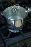 Saucepan on a gas cooker hob Stock Photography