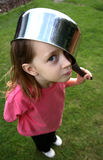 Saucepan on head. Young girl with a saucepan on her head royalty free stock photography