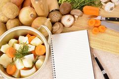 Saucepan with organic vegetables and herbs on kitchen worktop with recipe book, copy space Stock Photography