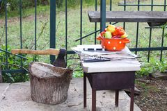Saucepan with peppers and an ax in a wooden deck Stock Photo