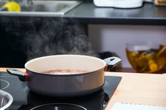 Saucepan on the plate. Saucepan with boiling clear soup on the plate stock photography