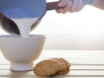 Saucepan pouring milk in bowl to breakfast Royalty Free Stock Image