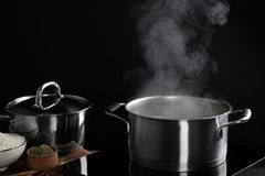 Saucepan with steam. On black background stock photo
