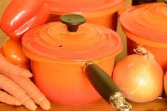 Saucepans and veggies. Bright orange saucepans  with vegetables Stock Image