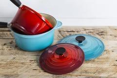 Saucepans. Colourful pots, pans and saucepans with lids Stock Photos