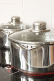 Saucepans on a halogen hob Stock Photography