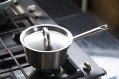 Saucepans on modern kitchen range. Stainless steel saucepans on modern kitchen range Stock Images