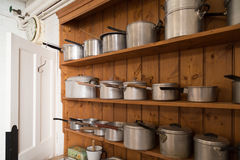 Saucepans on shelf. Collection of vintage saucepans on wooden kitch dresser Royalty Free Stock Photo