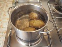 Saucepot med potatisar på spisen Arkivfoto