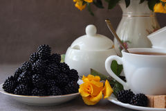 Saucer with blackberry. And cup of tea on a background of a bouquet of roses Stock Image