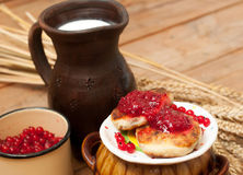 A saucer of cheese cakes with fruit jam, a crock of milk, a metal cup of ripe red currants and mature ears on a wooden surface Royalty Free Stock Photo