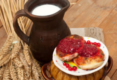 A saucer of cheese cakes with fruit jam, a crock of milk, a metal cup of ripe red currants and mature ears on a wooden surface Stock Photography