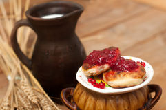 A saucer of cheese cakes with fruit jam, a crock of milk, a metal cup of ripe red currants and mature ears on a wooden surface Stock Photos
