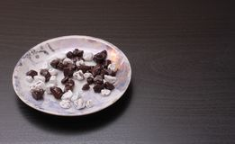 Saucer with chocolate pieces. Saucer with chocolate chips on a brown background Stock Images