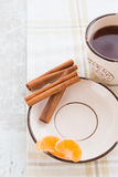 Saucer with cinnamon and tangerine. Saucer with cinnamon sticks and tangerine Royalty Free Stock Image