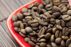 Saucer and coffee beans on a bamboo mat Stock Image