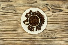 On a saucer with coffee beans there is a cup with coffee beans Stock Photo