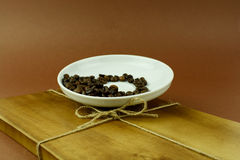 Saucer with coffee beans on wooden cutting board with a bow.  Stock Images