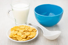 Saucer with corn flakes, empty blue bowl, milk and spoon Royalty Free Stock Images
