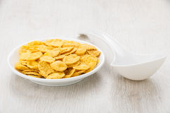 Saucer with corn flakes and white plastic spoon on table Royalty Free Stock Images