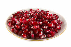 Saucer filled with pomegranate berries. Isolated on the white Stock Images