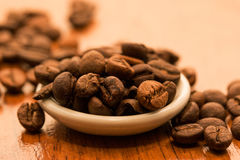 A saucer full of fragrant coffee beans Royalty Free Stock Images