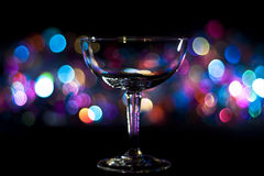 Saucer glass against bokeh background. A champagne saucer glass against a colourful bokeh background Stock Images