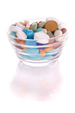 Saucer with many-colored pills. Transparent saucer with many-colored pills with reflection Royalty Free Stock Images