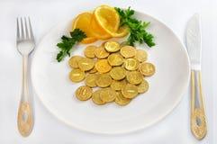 Geld prägt auf weißer Platte mit Gabel und Messer, ist Stockbild