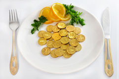 Money coins on white plate with fork and knife, is Stock Image
